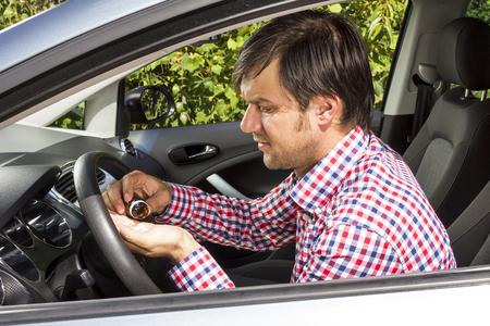 Closeup of young man taking pills inside his car
