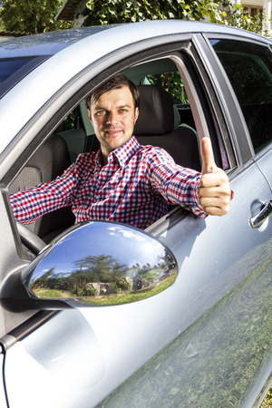 atractive: Happy young man with thumb up at the wheel of his car Stock Photo