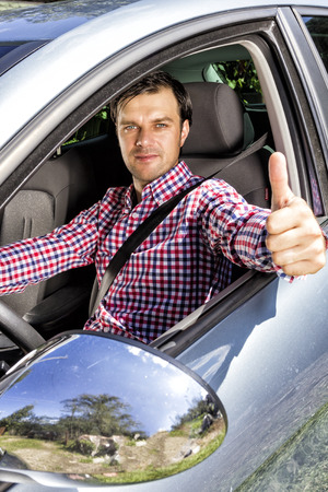 automobile insurance: Happy young man with thumb up at the wheel of his car Stock Photo