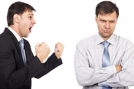 miffed: Portrait of two businessmen having a confrontation isolated on white background.Conceptual image