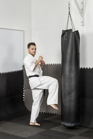 forceful: Athletic black belt karate giving a forceful knee kick during a training sesion with a boxing bag Stock Photo
