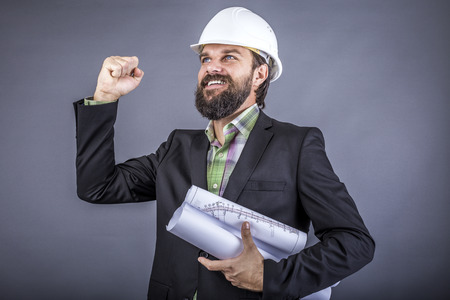 Successful engineer celebrating with arm up over gray background