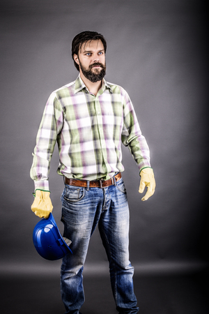 work gloves: Portrait of young engineer holding his hardhat in one hand over gray background Stock Photo