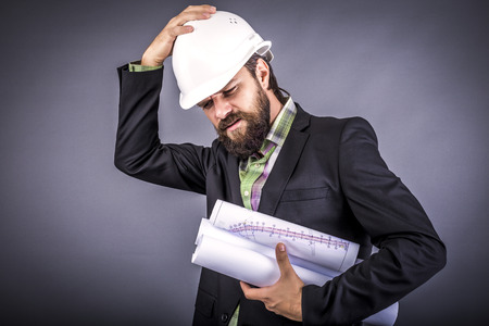 Overwhelmed businessman with hardhat over gray background
