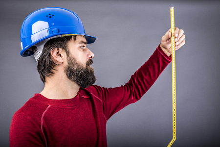 centimetre: Happy young engineer with hardhat holding a measuring tape over gray background Stock Photo