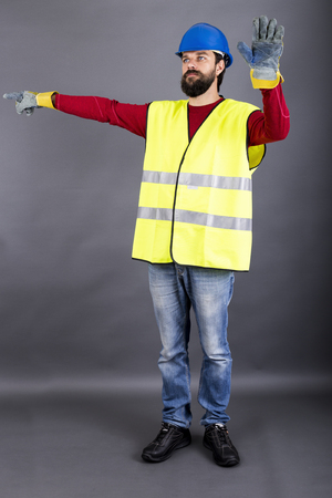 Young construction worker with hardhat directing traffic, showing  stop sign over gray background