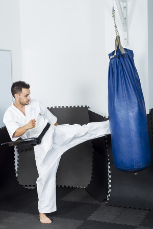 forceful: Athletic karate fighter giving a forceful foot kick to a heavy bag during his training