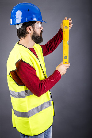 nivelador: Young engineer with hardhat and reflective vest holding a leveler over gray background