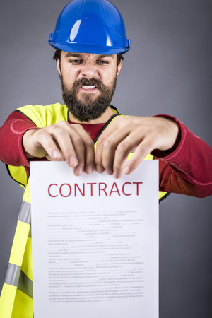 disapprove: Frustrated young engineer with hardhat and reflective vest  tearing apart a contract over gray background