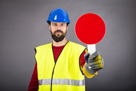 warning vest: Young construction worker with hardhat stopping traffic ,holding a stop sign over gray background Stock Photo