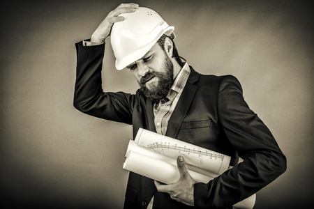 overwhelmed: Overwhelmed businessman with hardhat over gray background