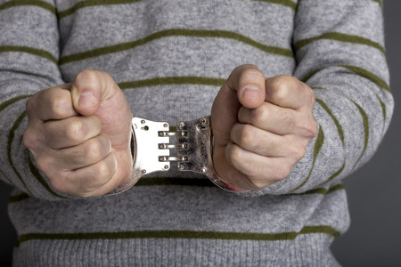 confiscation: Conceptual image of an arrested man with handcuffs