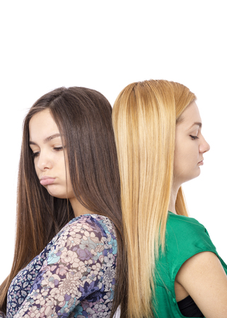 two face: Closeup portrait of two sulky teenage girls standing back to back over white background
