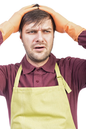 unhappy man: Overwhelmed young man with apron and gloves holding hands on head over white Stock Photo