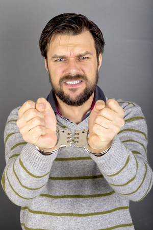 handcuffed hands: Closeup portrait of a young man with hands handcuffed over gray background Stock Photo
