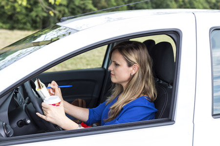 Beautiful young woman working and drinking coffee while driving Stock Photo
