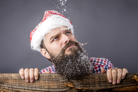 miffed: Closeup portrait of a sad bearded man with santa cap looking up. Christmas time Stock Photo