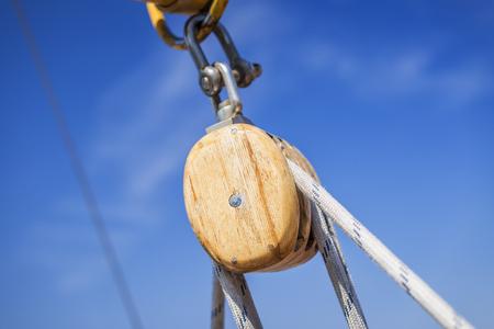 polea: Polea de madera con cuerdas bajo el cielo azul claro Foto de archivo