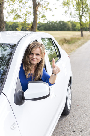 adentro y afuera: Happy young woman with thumb up at the wheel of her new car