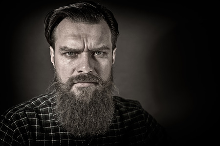 Closeup portrait of a bearded man with angry look on gray background