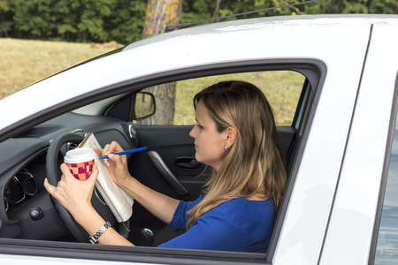 Beautiful young woman working and drinking coffee while driving photo