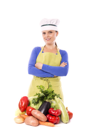 Beautiful young chef  next to her fresh vegetables on white background photo