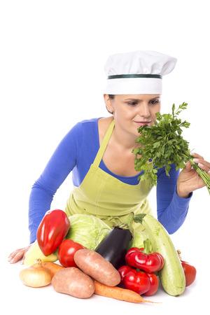 Beautiful young chef  holding fresh parsley on white background photo