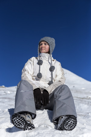Young woman sitting on top of a snowy mountain admiring the view Stock Photo