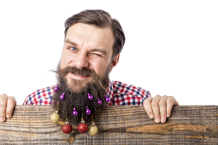 Closeup portrait of a funny man with decoration balls in his beard over white background photo