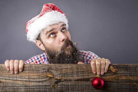 Portrait of a funny bearded man with santa cap holding a red round decoration ball over gray background photo
