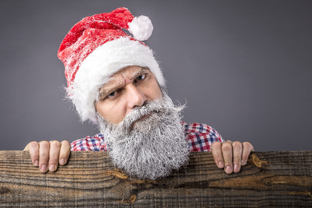 Closeup of a  man with frozen beard wearing santa red cap looking over the fence.Winter and Christmas time photo
