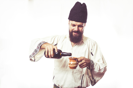 Young man wearing traditional Romanian costume on white background holding a bottle of wine