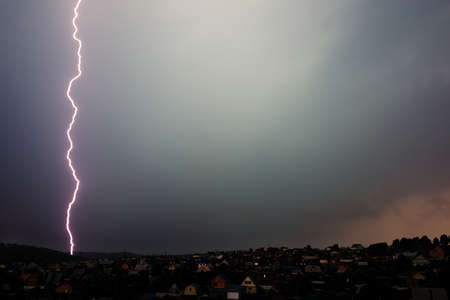 struck: Lighting bolt struck down the village with the gloomy sky in background