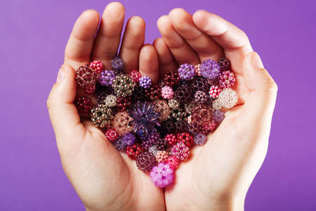 seed beads: Hands with hand-woven beads in the shape of heart Stock Photo