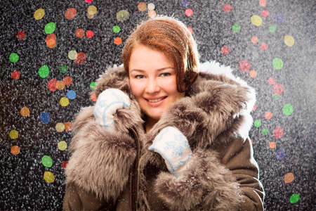 colorfuls: Ginger girl in fur coat wearing mittens with snow and colorfuls lights in the background Stock Photo