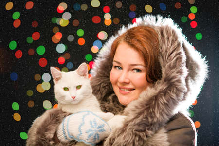 colorfuls: Ginger girl in fur coat wearing mittens holding white cat with snow and colorfuls lights in the background