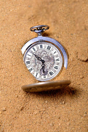 Vintage pocket watch on the beach buried in a sand Stock Photo