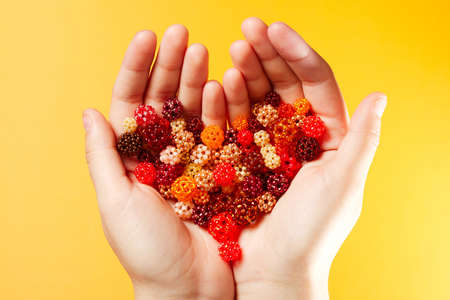 seed beads: Hands with a lot of hand-woven spheres in the shape of heart, every ball made of tiny glass seed beads, on yellow background Stock Photo
