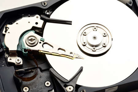 internals: Computer hard disk drive internals with exposed disc surface and heads close up