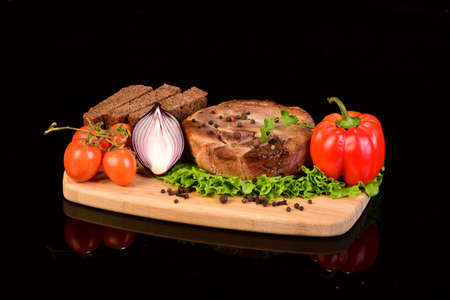 Tasty meat medallion, lettuce, onion, pepper, cherry tomatoes and slices of bread on a wooden cutting board