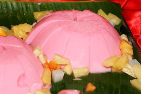 Jelly  cake   with  pineapple  and papaya   on  green  plate   photo