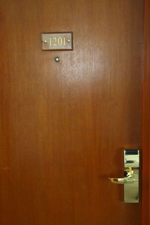 hotel room door   with gold  number  plate