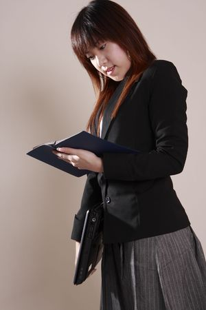 entrepeneur: asian  businesswoman see the record  notebook in  office