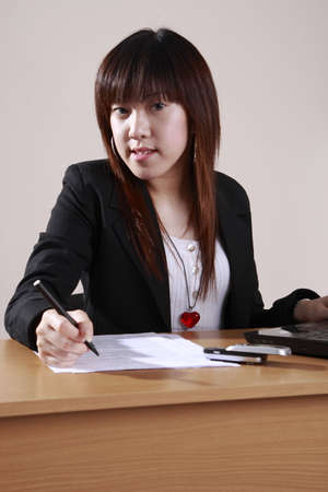 femme d affaires writting les documents dans le bureau