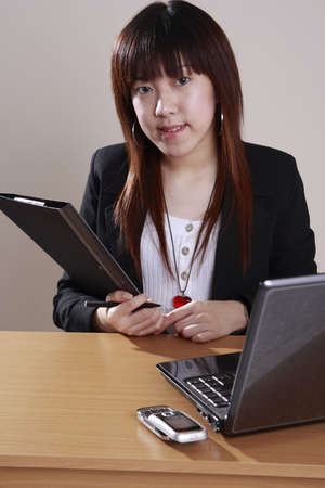 businesswoman holding a file   infront  the  laptop