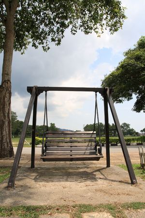 a wooden swing  at the park  under the big tree photo
