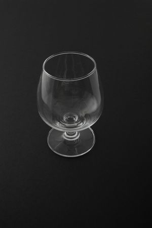 Empty  glass   cup    isolated   on    a   black    background  Stock Photo