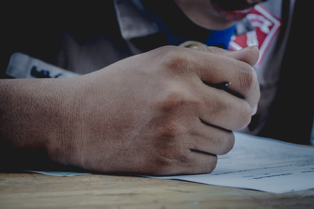Closeup to hand of student holding pen and taking exam in classroom with stress for education test. Standard-Bild - 93775823