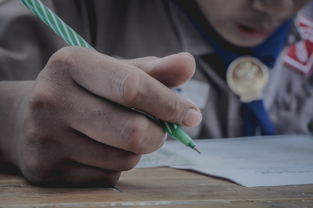 Closeup to hand of student holding pen and taking exam in classroom with stress for education test. Standard-Bild - 93803986