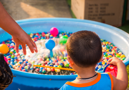 Kid is choosing the ball in the basin. Stock Photo